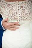 Groom hand on brides dress Royalty Free Stock Image