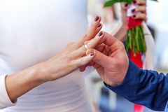 Groom hand putting wedding ring on bride finger. Bride and groom marriage hands with wedding rings. Groom hand putting wedding ring on bride finger. Declaration stock images