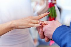 Groom hand putting wedding ring on bride finger. Bride and groom marriage hands with wedding rings. Groom hand putting wedding ring on bride finger. Declaration stock image
