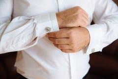 Groom hands with cufflinks. Elegant gentleman clother, white shirt Stock Images
