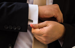 Groom hands fixing his cull links. Before ceremony stock images