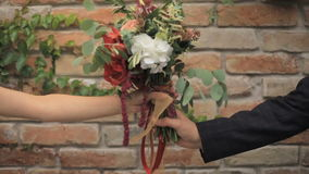 Groom hands over the bouquet to the bride against the brick wall background stock video