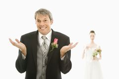 Groom with hands up. Caucasian groom in foreground with hands raised in air and Asian bride in background Royalty Free Stock Photography
