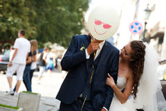Groom has fun while hiding behind a smiling balloon Stock Image
