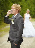 Groom has turned away from bride - speaks on phone Royalty Free Stock Photography