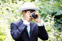 The groom in a hat with a camera Stock Images