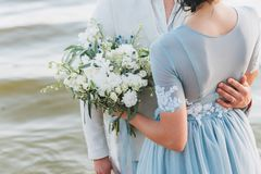 Groom having his hand on his bride`s waist, standing on a beach. Bride is holding a bouquet. royalty free stock photography