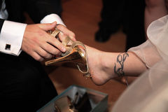 A groom help the bride with shoe. Woman foot with a tattoo Stock Photos