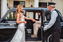 Groom helping bride to enter the car Royalty Free Stock Image