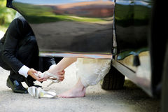 Groom helping bride to put her shoes on Stock Photo