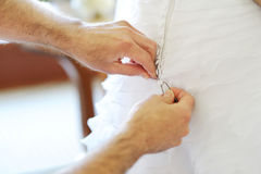 Groom helping bride to put  wedding dress on Stock Photo