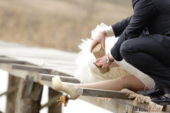 Putting on Wedding Shoe Stock Photography