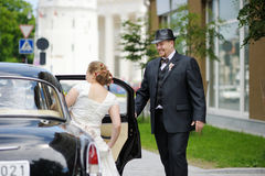 Groom helping his bride to get into a car Stock Photos