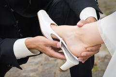 A groom helps the bride with shoe Royalty Free Stock Photography
