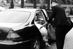 Groom helps bride to go out of the black Mercedes Stock Images