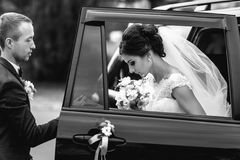 Groom helps bride to step out of the black car Stock Image