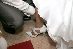 Groom helps the bride to wear shoes Royalty Free Stock Photography