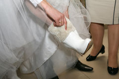 Groom helps the bride wear the boots Stock Photo