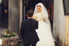 Groom helps charming bride to step out the door Royalty Free Stock Images