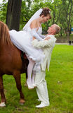 groom helps fiancee to get down from a horse Royalty Free Stock Photos