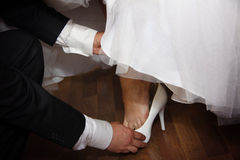 Groom helps his bride with shoe Stock Photos
