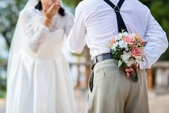 Groom hide flower bouquet his back to offer to bride for surprise Stock Images