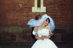 Groom hides behind bride`s veil posing outside the cathedral stock images