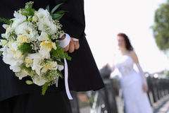 Groom hides bouquet for bride. Newlyweds walk during their wedding day Royalty Free Stock Photo