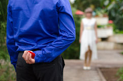 Groom hiding the wedding ring behind his back and going to offer it to a bride. Royalty Free Stock Photos