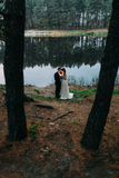 Groom and his charming wife kissing on the shore of forest lake holding burning candle at evening Royalty Free Stock Photo