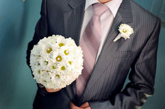 Groom hold wedding bouquet in his hand for bride Royalty Free Stock Photography