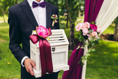 Groom hold wedding box with flower and lilac ribbon on wedding  Stock Photo