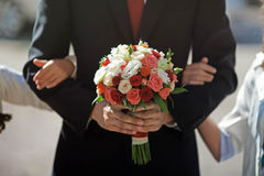 Groom is holding an amazing splendid wedding bouquet of pink re. D and beige roses Stock Images
