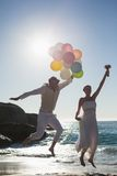 Groom holding balloons and bride holding bouquet jumping Stock Image