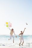 Groom holding balloons and bride throwing her bouquet jumping Royalty Free Stock Photo