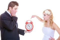 Groom holding big red clock yelling and bride stock photography