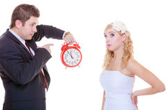Groom holding big red clock yelling and bride Stock Image