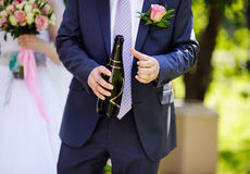 Groom holding bottle with champagne Royalty Free Stock Photo