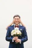 Groom holding  bouquet   bride closes his eyes with hands Stock Images