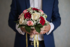 Groom holding a bouquet. Of white, peach and red roses Royalty Free Stock Photos