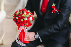 Groom is holding bridal bouquet Royalty Free Stock Photo