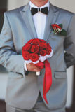 Groom holding bridal bouquet Royalty Free Stock Photography