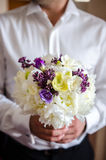 Groom holding the bride bouquet Royalty Free Stock Photography