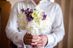 Groom holding the bride bouquet Stock Image
