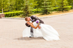 Groom holding bride in dance pose on wedding day Royalty Free Stock Photos