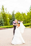 Groom holding bride in dance pose on wedding day Stock Image