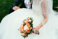 Groom holding a bride hand with weding bouquet on wedding day Stock Photo