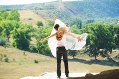 Groom Holding Bride in Hands. At sunny day Royalty Free Stock Photo