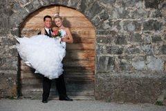 Groom holding a bride infront of wooden door Royalty Free Stock Image