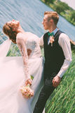 Groom holding bride near pond Royalty Free Stock Photography